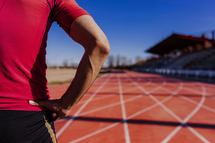 Midsection of athlete exercising on sports track
