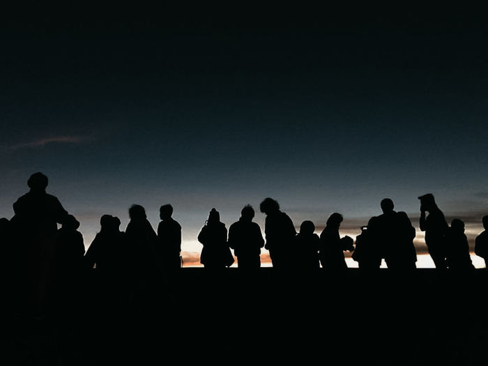 Silhouette of people looking at sky