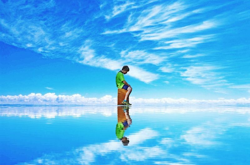 Digital composite image of boy sitting on stool in sea against sky