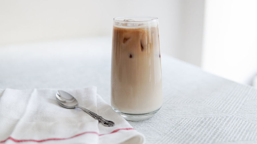 milk and iced coffee on white table Close-up Coffee Coffee - Drink Drink Drinking Glass Eating Utensil Focus On Foreground Food And Drink Glass Household Equipment Indoors  Kitchen Utensil Latte No People Paper Refreshment Spoon Still Life Table Tablecloth Textile