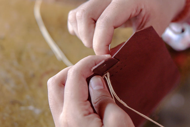 Close-up of woman hands making leather wallet in workshop