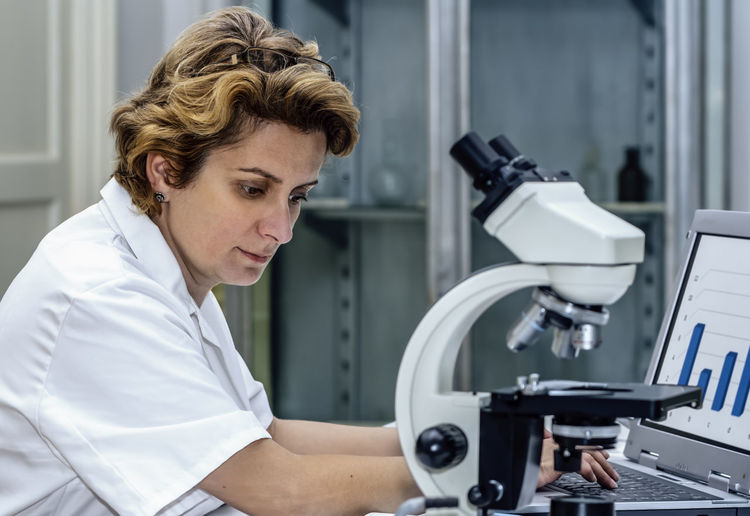 Close-up of scientist using laptop while sitting at laboratory
