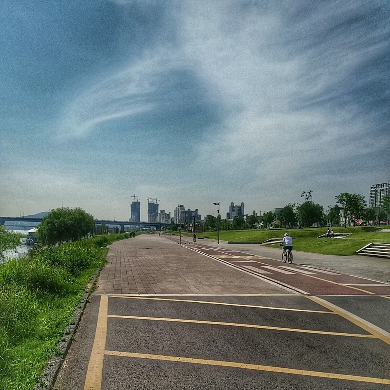 architecture, built structure, sky, building exterior, city, cloud - sky, skyscraper, day, tree, transportation, outdoors, modern, real people, road, travel destinations, growth, cityscape, urban skyline, full length
