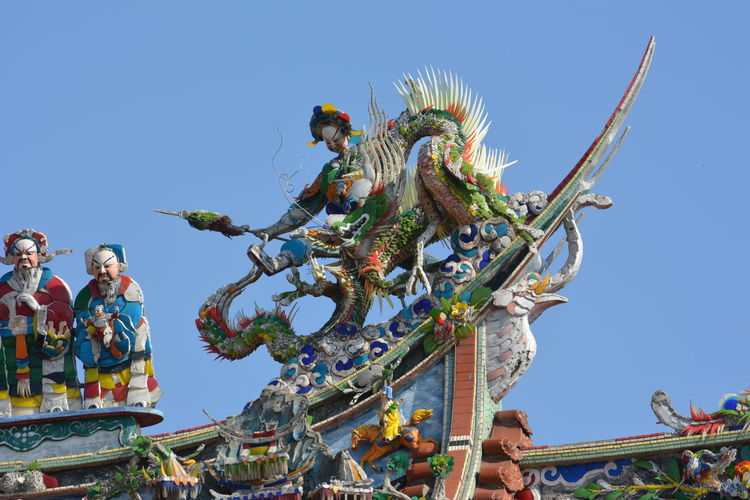 The very intricate details of a Taiwanese temple building Architecture Asian Culture Buddhist Temple Celebration Ceremony Chinese Statue Clear Sky Colourful Day Decoration Figurines  Intricate Details No People Outdoors Roof Rooftop Sky Statue Statue Temple No People Outdoors Dragon Colourful Colorful Daoism