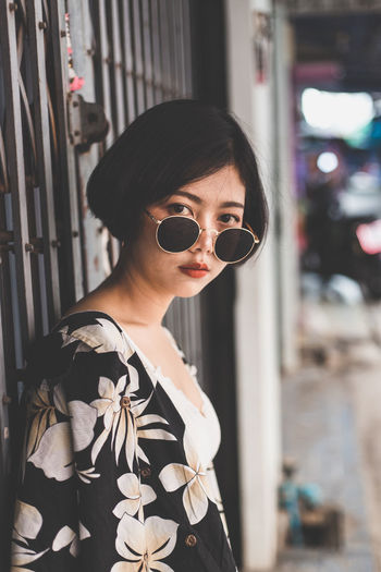 Portrait of young woman wearing sunglasses while standing against gate
