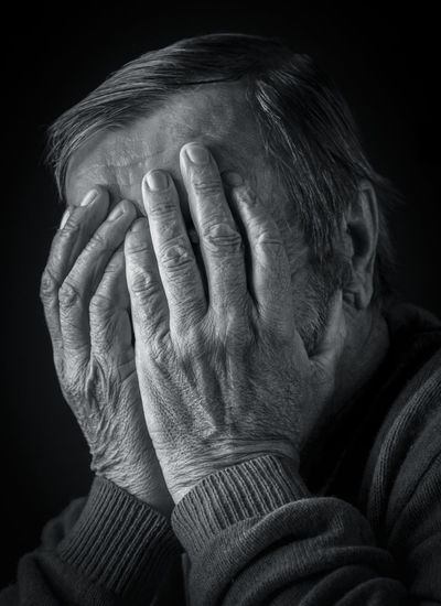 Elderly man covered his face with his hands, black and white portrait