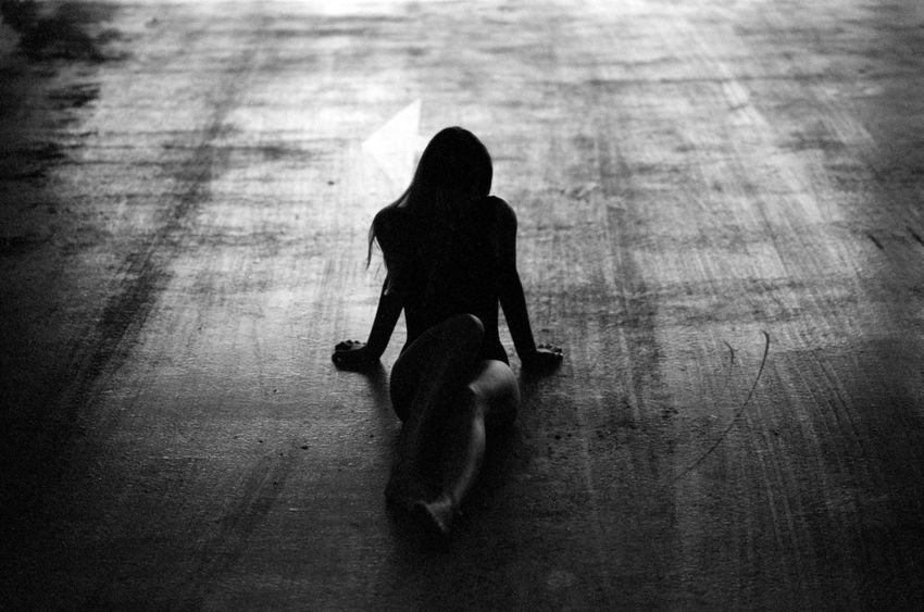 Adult Analog Blackandwhite City Concrete Day Depression - Sadness Flooring Full Length High Angle View Indoors  Leisure Activity Lifestyles One Person Real People Shadow Silhouette Sitting Solitude Walking Women Wood - Material