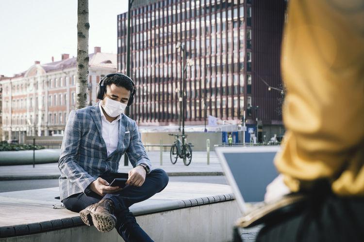 Full length of man sitting on mobile phone in city