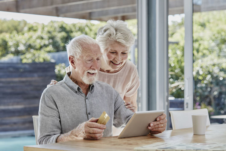 Couple holding mobile phone while sitting on table