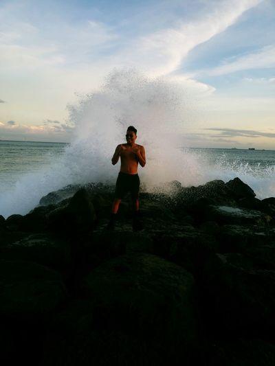 Shirtless man standing against splashing wave at beach