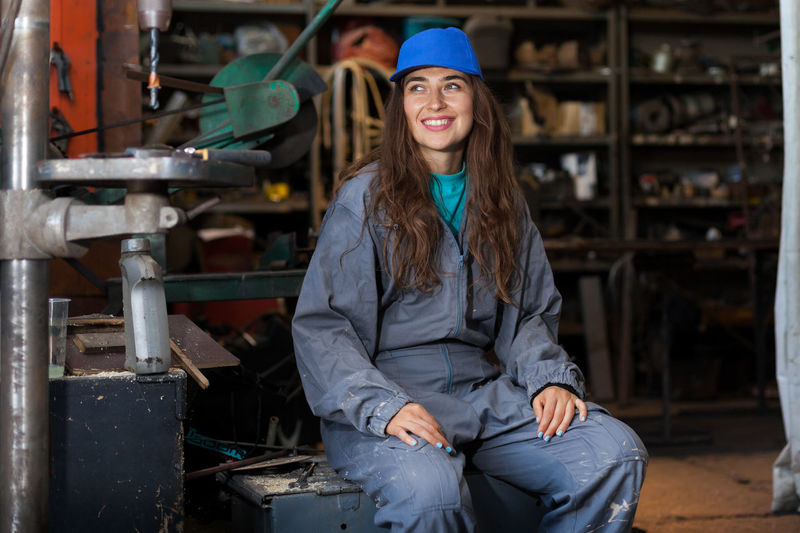 Smiling Woman In Uniform Sitting In Workshop