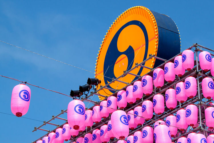 Low angle view of japanese lanterns and symbol against blue sky
