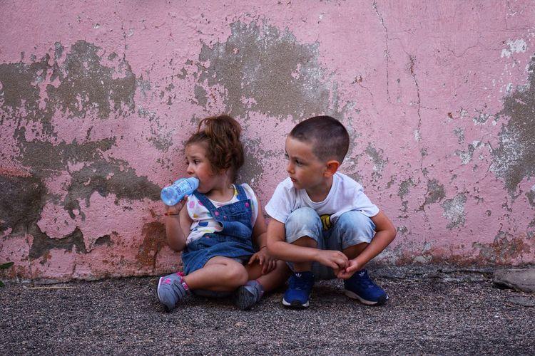 Siblings sitting on wall
