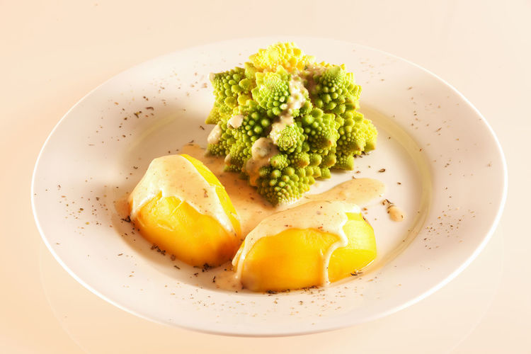 One serving Romanesco with boiled potatoes and cheese sauce on a large white plate, isolated on white, Brassica Oleracea Convar Dinner Dish Lunch Vegetarian Food Boiled Potatoes Cauliflower Cheese Sauce Close-up Food Food And Drink Freshness Healthy Healthy Eating Indoors  No People Plate Potatoes Ready-to-eat Romanesco Sauce Studio Shot Vegetarianfood White White Background