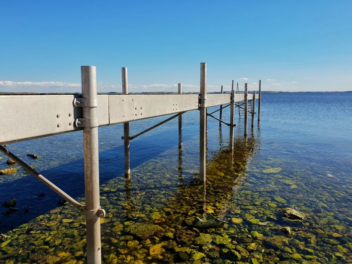 Wooden posts in sea against clear blue sky