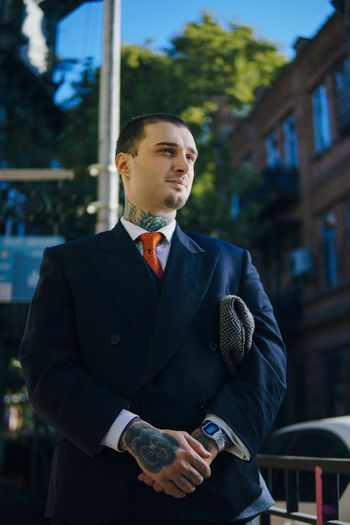 Thoughtful young male model wearing suit while standing outdoors