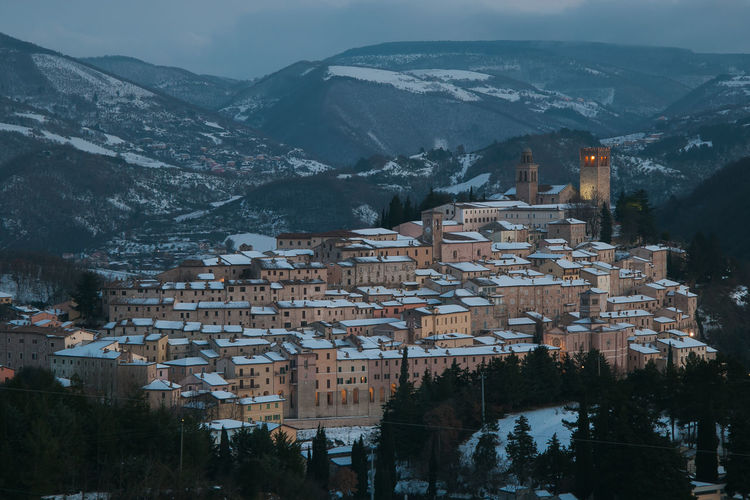 Aerial view of townscape by mountains during winter
