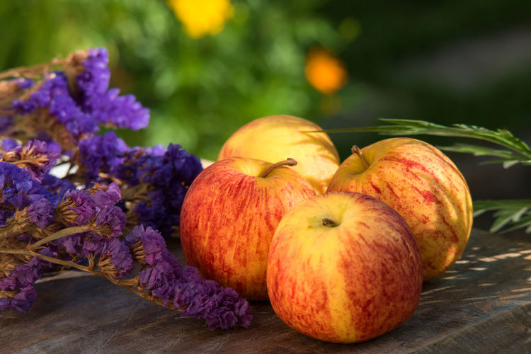 Close-up of purple flowers with apples on wooden table