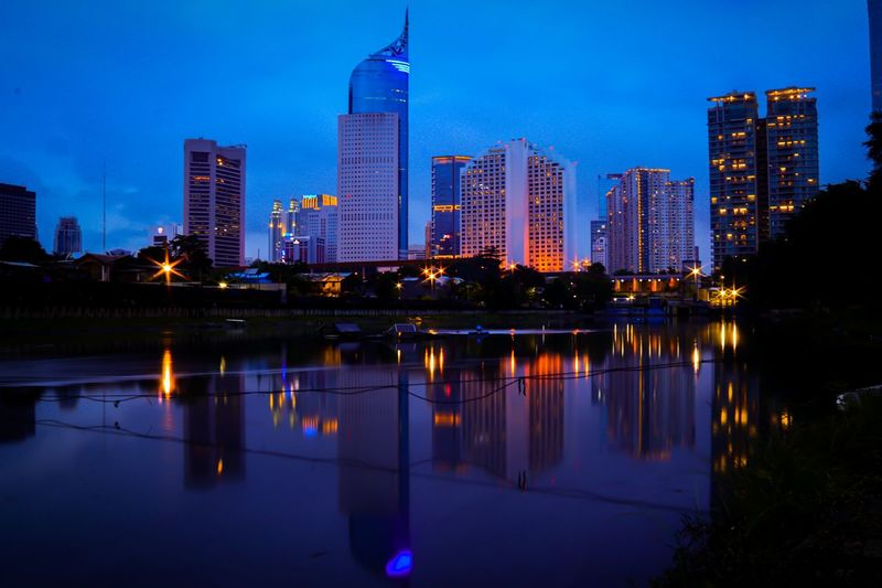 Reflection of illuminated buildings in city at dusk