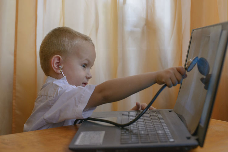 Boy Wearing Stethoscope While Using Laptop At Table