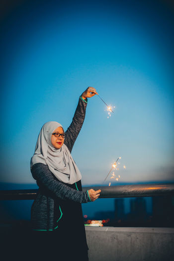 Woman with burning sparklers against blue sky at dusk