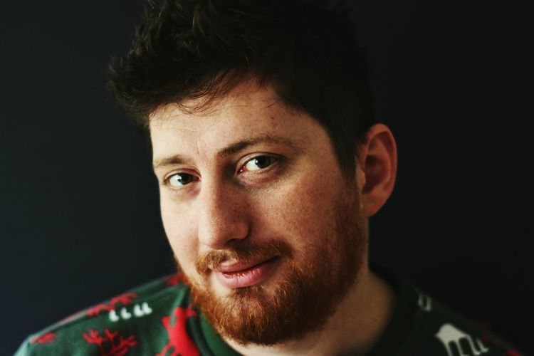 Portrait of smiling bearded man against black background