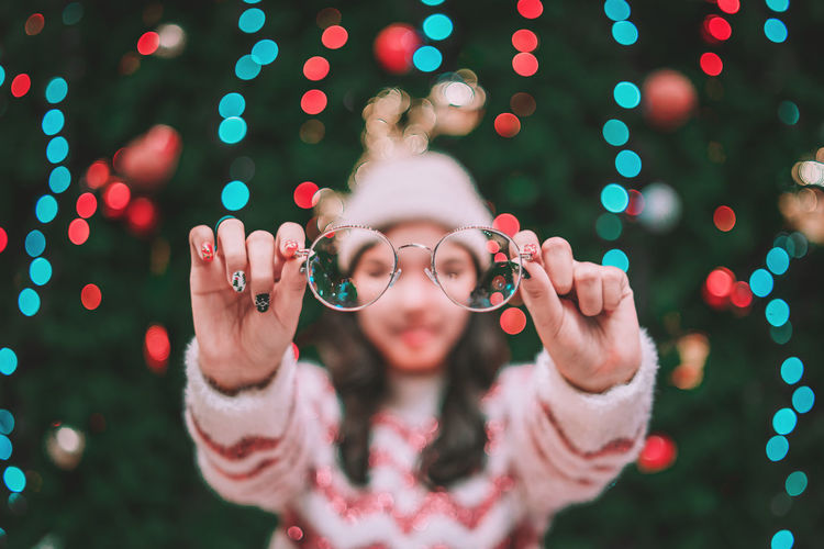 Woman holding eyeglasses while standing by christmas tree