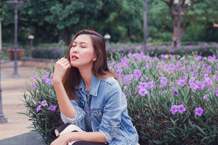 Beautiful young woman on purple flowering plants