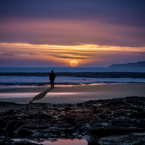 Silhouette man standing on sea shore at beach during sunset