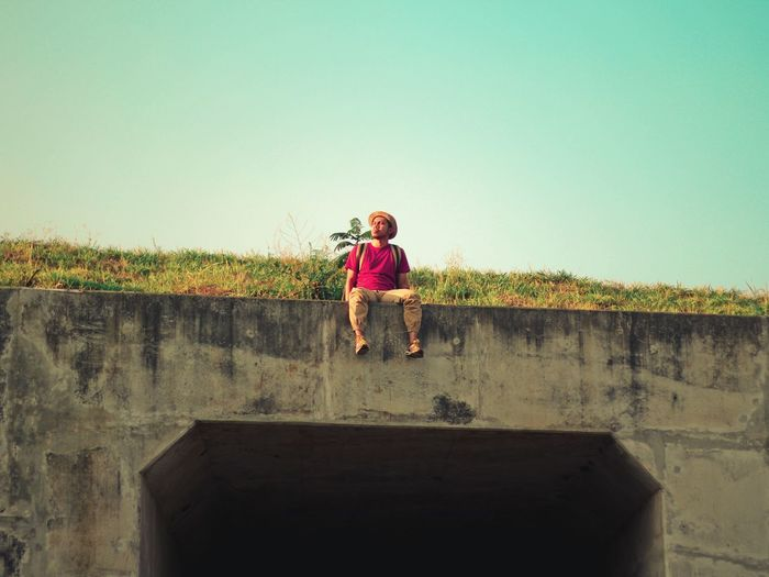 Full Length Of Man Sitting On Retaining Wall Against Clear Sky