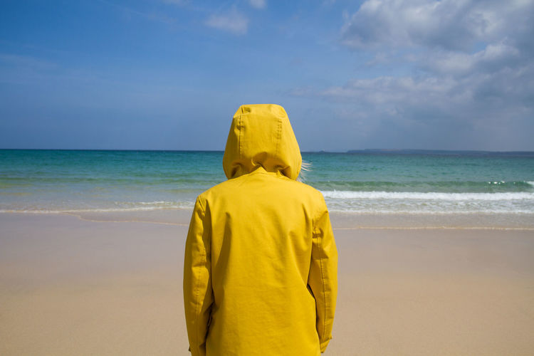 A rear view of a lone woman in a bright yellow hooded jacket on a deserted sandy beach and looking out to sea. Adult Beach Beauty In Nature Coat Day Hooded Shirt Horizon Over Water Lifestyles Lonely Nature One Person One Woman Only Outdoors People Real People Rear View Sand Scenics Sea Sky Solitary Standing Water Wave Yellow