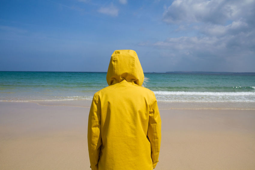 The rear view of a lone woman on a sandy beach in summertime, wearing a bright yellow hooded jacket and facing the ocean under a blue sky. Alone Beach Beach Life Beach Photography Beachphotography Bright Colors Cornwall Day Girl Hoodie Nature Ocean Ocean View One Person One Woman Only Outdoors Rear View Sandy Beach Sea Seaside Sky St Ives Vacation Woman Yellow Paint The Town Yellow