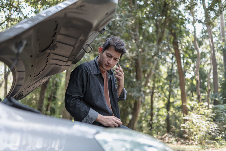 Man talking on while standing by broken vehicle against trees