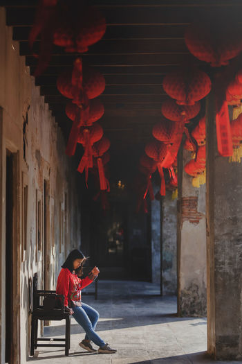 A lonely red dress girl sitting on a chinese wooden chair waiting for someone