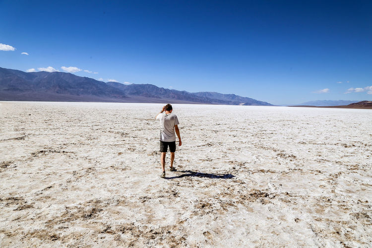 man walking in badwater basin in death valley national park Walking Around Badwater Basin Death Valley National Park Desert Exploring Hiking Man Walking From Behind Salt Flats Adventure Arid Climate Full Length Landscape Leisure Activity Lifestyles Man Walking Alone Mountain Mountain Range Nature Non-urban Scene One Person Outdoors Real People Rear View Salt Flat Sky Tranquil Scene Salt Basin Pursuit - Concept Hiker Arid Landscape