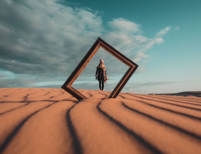 Woman standing on wood against sky
