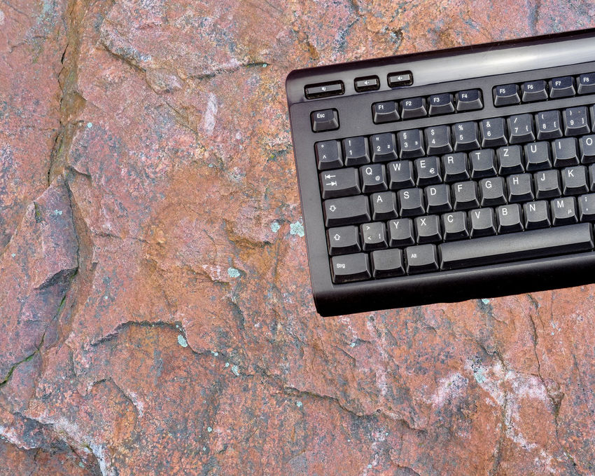 Computer keyboard of a computer in front of a background from a raw red sandstone plate, isolated, photomontage Isolated Photomontage Raw Red Abstract Background Close-up Combine Computer Key Computer Keyboard Concept Day Indoors  Keyboard No People Office Plate Sandstone Technology