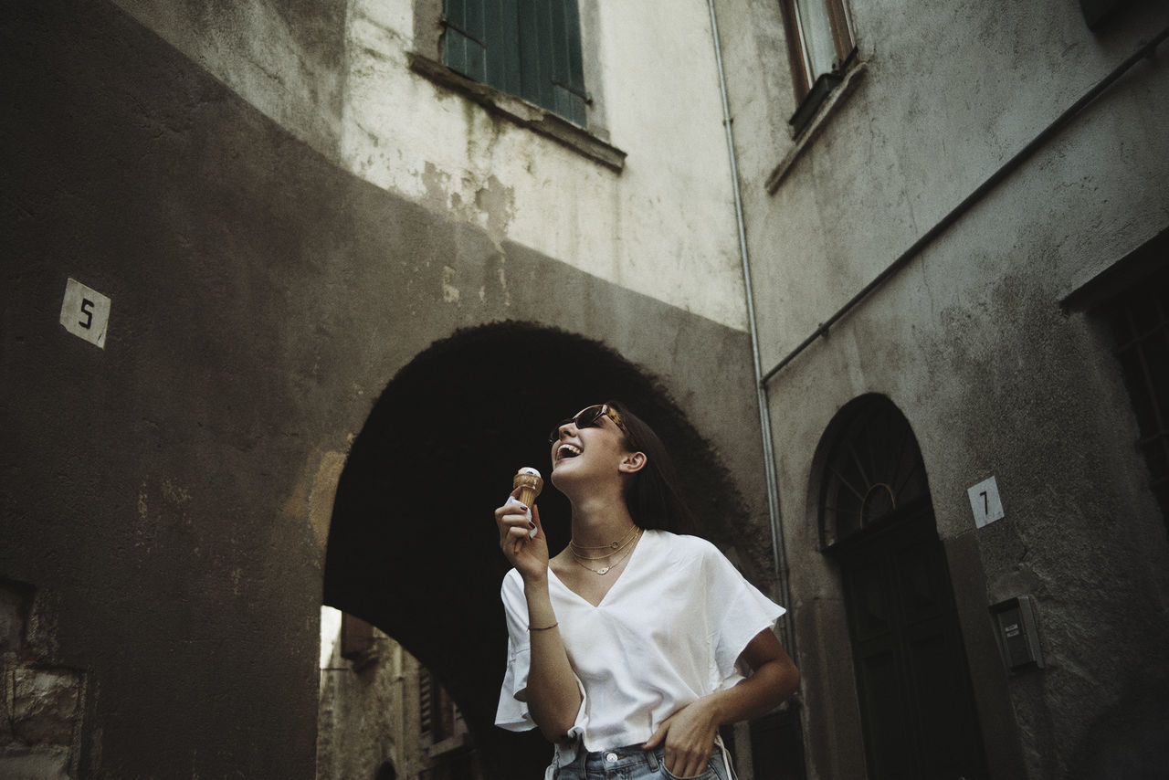 Young woman with ice cream standing against built structure