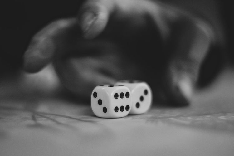 Close-up of hand holding dices on table