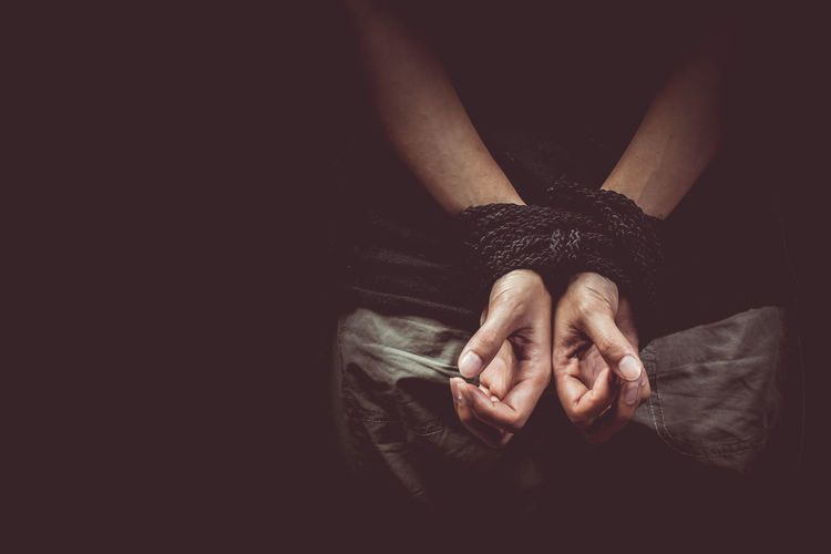 Close-up of man hand tied with rope against black background