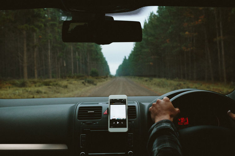 Audiobook Dashboard Driving Driving Forest Forrest Journey Leisure Activity Lifestyles Mode Of Transport Photography Themes Podcast Road Trip Smart Phone Tree Windshield First Eyeem Photo