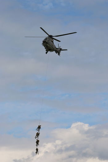 Army soldiers on rope hanging from helicopter against sky