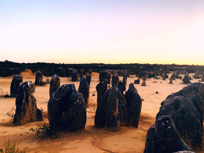 Panoramic view of rocks on beach against sky during sunset