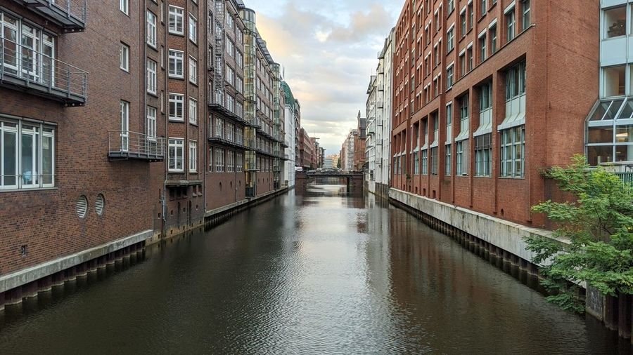 Canal amidst buildings against sky