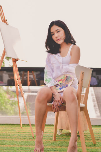 Adult Beautiful Woman Casual Clothing Chair Easel Front View Hairstyle Holding Leisure Activity Lifestyles Looking At Camera One Person Portrait Real People Seat Sitting Three Quarter Length Women Young Adult Young Women