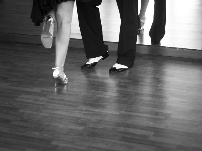 Low section of woman and man standing on hardwood floor