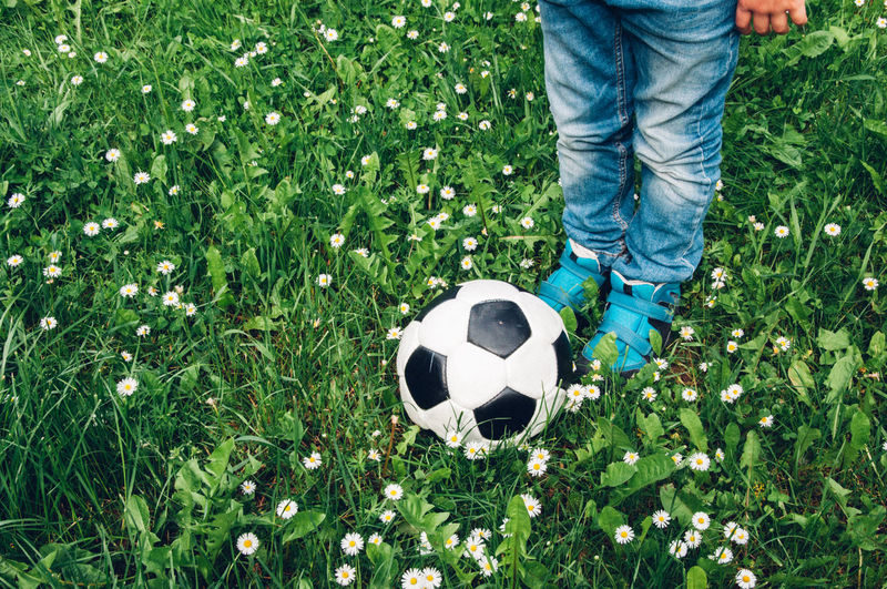 Low Section Of Boy Standing By Soccer Ball On Grassy Field