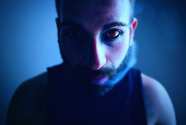 Close-up of spooky man smoking while wearing red contact lens in darkroom