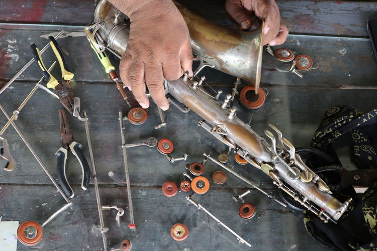 Cropped hands of man repairing musical instrument in workshop