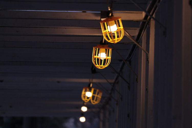 Illuminated light bulbs hanging on ceiling at night